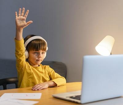 طفل يرفع يده أثناء ممارسة التعليم عن بعد أمام جهاز لاب توب